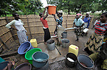 "A woman gets help from other women to lift a water container on her head, after filling it at the village pump in Chidyamanga, a village in southern Malawi that has been hard hit by drought in recent years, leading to chronic food insecurity, especially during the ""hunger season,"" when farmers are waiting for the harvest."