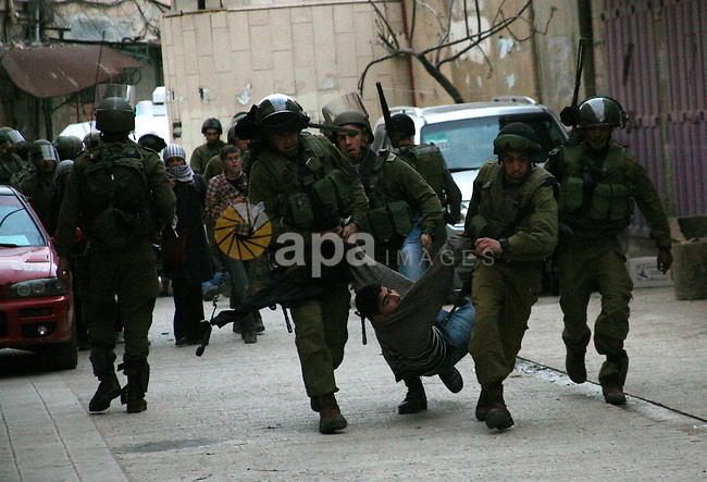 Israeli policemen and soldiers detain Palestinian protesters and foreign activists on April 01, 2012, after they took refuge in an abandoned house and fly a Palestinian flag on the rooftop of the building near the Beit Romano area that several hundred Jewish settlers reside, in the West Bank town of Hebron. Photo by Mamoun Wazwaz