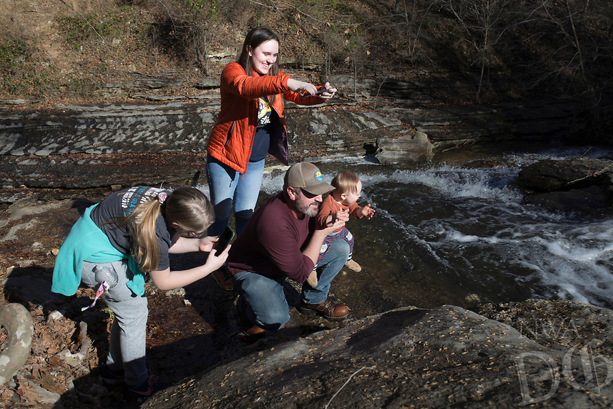 NWA Democrat-Gazette/CHARLIE KAIJO Kinzie Bailey, 9 and Kendrick Bailey, 17, (from left) take pictures as Bryan Bailey of Bentonville holds Woodrow Bailey, 1, over a creek, Saturday, January 5, 2019 at Tanyard Creek Nature Trail in Bella Vista.