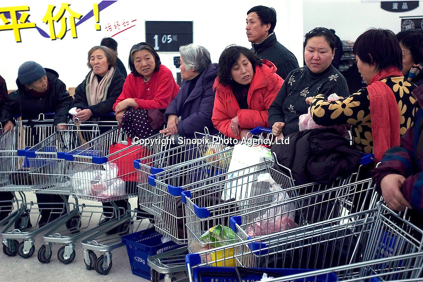 Consumers line up for about 2 hours to buy mutton slices in a newly opened Wal-Mart Supercenter in Harbin, Heilongjiang province, China. The Wal-Mart price of mutton slices is 20% cheaper than that in common market in Harbin..27-DEC-04