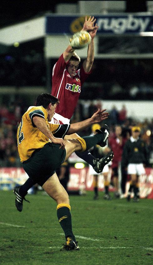 Photo. Richard Lane. .Lions Tour 2001. First Test, Australia v The Lions at the Gabba, Brisbane, Australia. 30/6/2001.Iain Balshaw charges down as Matt Burke clears.
