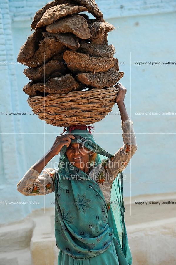 INDIA Uttar Pradesh , dalit women in village in Bundelkhand, woman carry cow dung on the head, the cow dung is used as cooking fuel  / INDIEN Uttar Pradesh, Frauen unterer Kasten und kastenlose Frauen, Dalits, in Doerfern in Bundelkhand, Frau traegt Kuhdung auf dem Kopf, die Kuhfladen werden als Brennstoff zum Heizen und Kochen verwendet