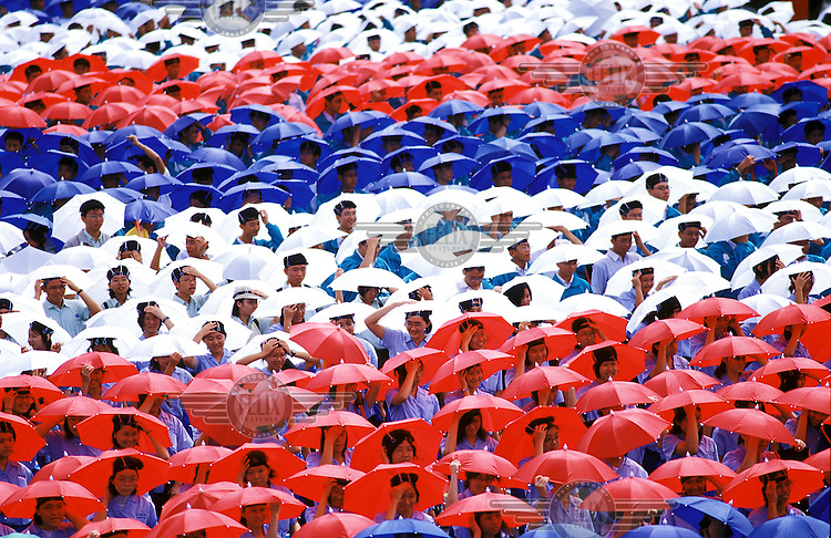 Students wearing coloured umbrella hats during the Taiwan National Day celebrations in Taipei on 10OCT02.  Credit: Chris Stowers.