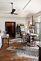 Terracotta herring-bone patterned floor in the living room with zepra skin rugs