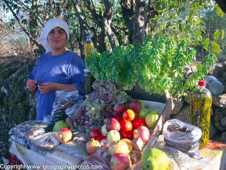 Woman selling fresh fruit from a roadside stall, Kayakoy village, Fethiye, Turkey