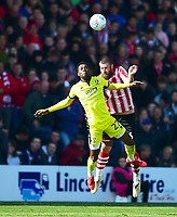 Lincoln City's Michael Bostwick battles with  Cheltenham Town's Rakish Bingham<br /> <br /> Photographer Andrew Vaughan/CameraSport<br /> <br /> The EFL Sky Bet League Two - Lincoln City v Cheltenham Town - Saturday 13th April 2019 - Sincil Bank - Lincoln<br /> <br /> World Copyright &copy; 2019 CameraSport. All rights reserved. 43 Linden Ave. Countesthorpe. Leicester. England. LE8 5PG - Tel: +44 (0) 116 277 4147 - admin@camerasport.com - www.camerasport.com