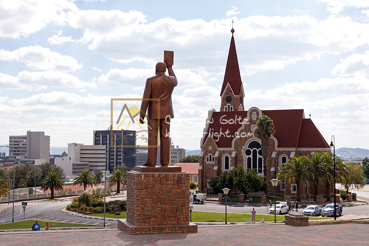 A statue of Sam Nujome holding the Namibian constitution stands in front of the Independence Museum in Windhoek. In the background modern Windhoek and the Christ Church.
