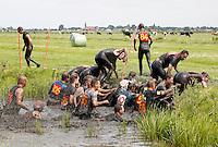 Nederland Schermerhorn 2016 07 10 . Jaarlijkse Prutmarathon door de modderige slootjes van de Mijzenpolder. Mensen helpen elkaar de sloot uit.  Foto Berlinda van Dam / Hollandse Hoogte