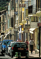 Shop signs, streetlamp globes and awnings form repeating pattern on commercial street sloping down to river. Strollers and parked cars. Backlit. Vaison la Romaine Provence France.