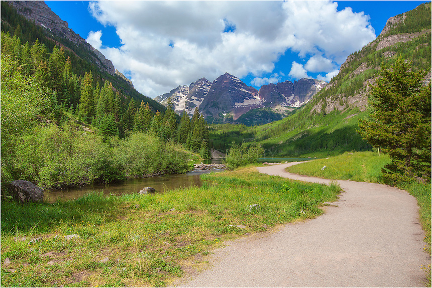 The drive from Highway 82 near Aspen to the Maroon Bells Wilderness Area is a beautiful, winding 8 mile road that passes through Aspen trees, meadowns, and follows Maroon Creek. After you park in the lot, you'll find yourself walking this path as the iconic Maroon Bells appear before you. Possibly the most photographed mountains and landscape in Colorado, these two 14,000 feet mountains rise above Maroon Lake, and 2.3 miles further, Crater Lake.
