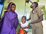 Feriska Christo (left) watches her daughter Nalima as Nyandeng Ring, a technician, weighs her during a periodic wellness exam at the St. Daniel Comboni Catholic Hospital in Wau, South Sudan.