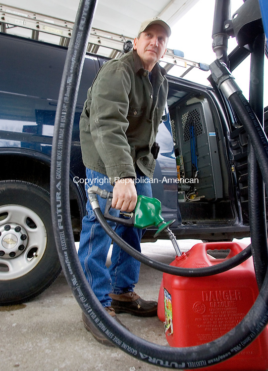 TORRINGTON CT. 26 January 2014-012615SV04-Mark Peterson of Canton fills up a gas can in Torrington Monday. Peterson was getting the gas for snow blowers; he does driveways as well flat roofs for businesses. <br /> Steven Valenti Republican-American