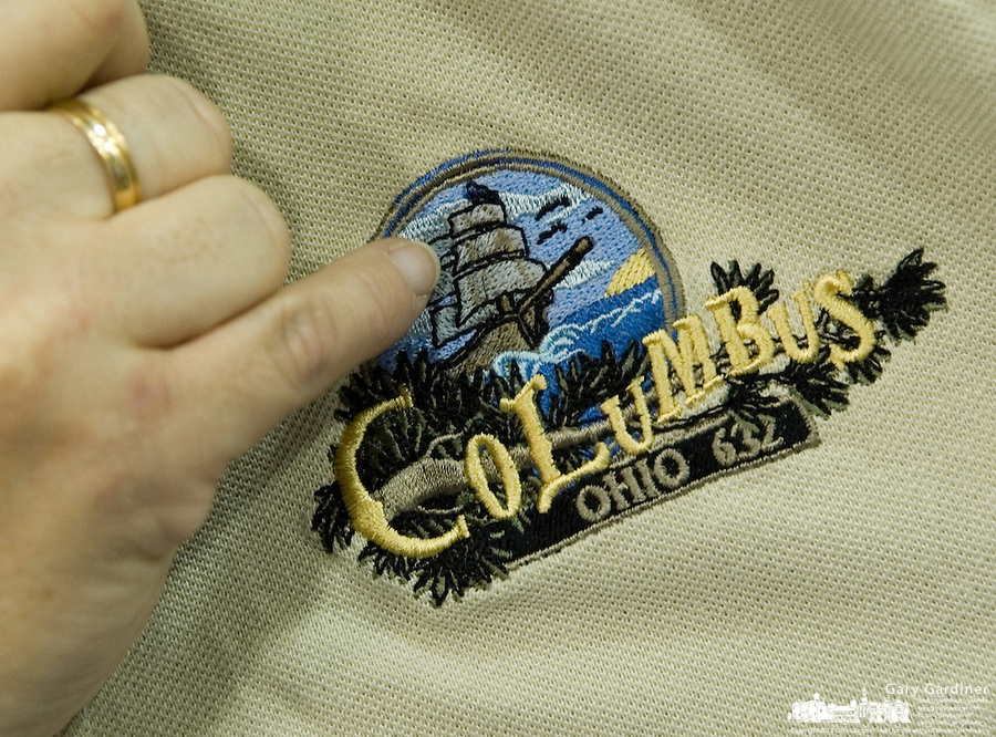 An employee explains the detail on the shirt given to workers at the 623rd Costco Wholesale store opening in Columbus, Ohio, Wednesday, Nov. 29, 2006.<br />