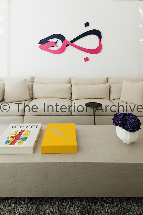 The living room has a predominately neutral palette with touches of colour provided by artworks and other items.