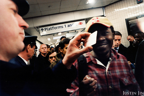 A ticket controller in London's Finsbury Park station checks the ticket of a passenger, who rode the metro with a ticket for children. The passenger lied about his age and was arrested by police. .Picture taken 2005 by Justin Jin