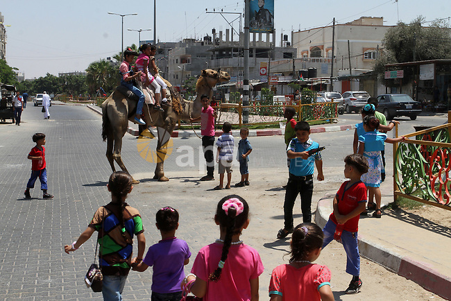 Palestinian children play on a street in Rafah in the southern Gaza strip on July 18, 2015, on the second day of Eid al-Fitr holiday which marks the end of the Muslim holy month of Ramadan. Photo by Abed Rahim Khatib