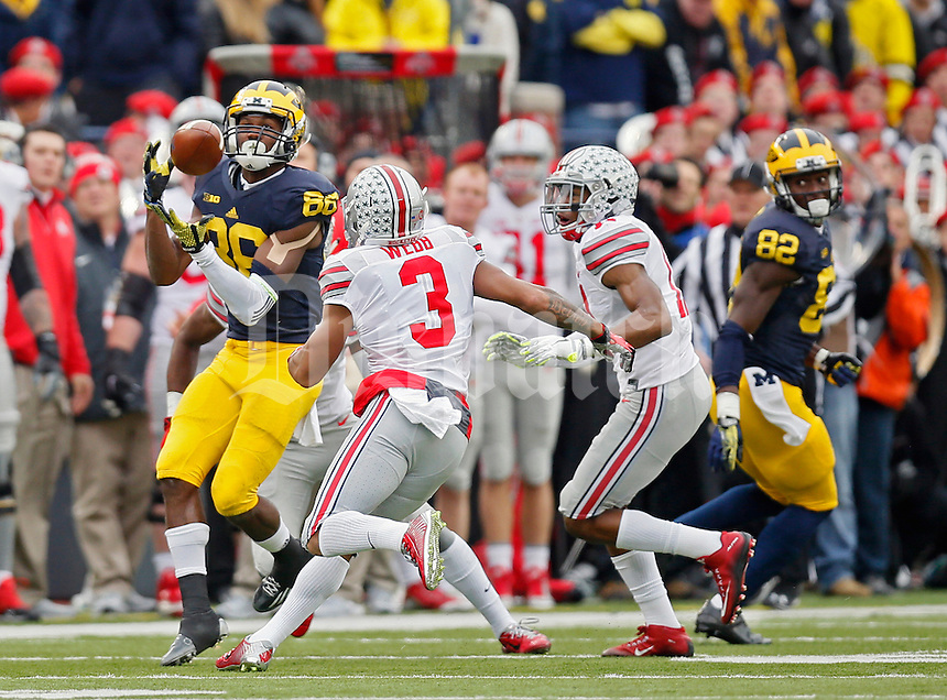 Michigan Wolverines wide receiver Jehu Chesson (86) makes a catch against Ohio State Buckeyes safety Vonn Bell (11) and cornerback Damon Webb (3) in the 2nd quarter at Michigan Stadium in Arbor, Michigan on November 28, 2015.  (Dispatch photo by Kyle Robertson)