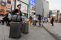 A Asian female tourist wheels suitcases through Shinjuku, Tokyo, Japan Friday June 30th 2017