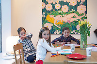 Sophie, Isabella and Imogen Cousins sitting at the dining table in their home in London. The painting behind is The Dream by Olga Vujadinovic