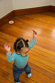 MR / Schenectady, NY. Toddler (1 year and 2 months old, African-American and Caucasian) in early walking stage holds her hands up as she walks. MR: Dal4. ID: AM-HD. © Ellen B. Senisi