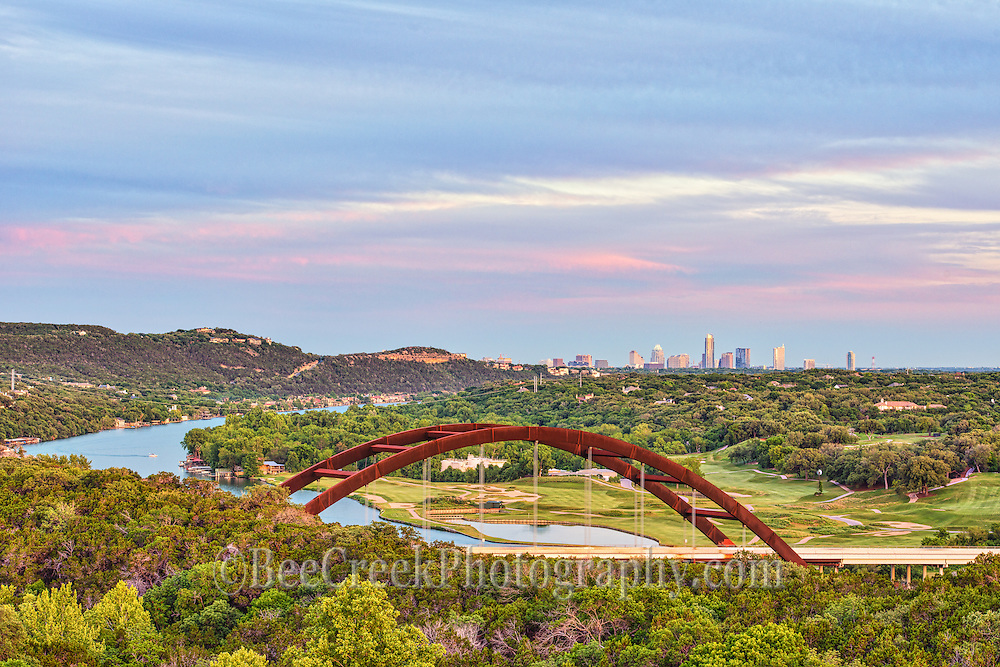 This is a photo with a bit of sunset colors over the city of Austin from the view of the Austin 360 bridge or  Pennybacker Bridge. It hard to get enough photo of this bridge. The Pennybacker Bridge with Lake Austin flowing underneath it a very scenic location to photograph. This day we had some interesting clouds and the austin city skyline in the background as the sun was setting in the sky.  The Austin 360 bridge is an iconic view of austin with the scenic blue waters of the lake meandering toward the city with all the greenery from the golf corse and trees with the Austin in the background.