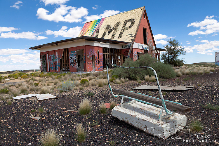 "Bench and campground store at Two Guns in Arizona. Two Guns is located in Arizona, east of Flagstaff, on what was formerly Route 66. Two Guns was originally called ""Canyon Lodge"" when the National Trail Highway moved westward. Later, the National Trail was re-named Route 66, the site's name was changed to Two Guns, because the proprietor of the facilities located there was one Henry E. Miller, who called himself ""Two Gun Miller."" During the heyday of Route 66, Two Guns became one of the numerous tourist traps along the way, with a gas station, overnighting accommodations, a food emporium, as well as a zoo. Two Guns went into decline with the building of the Interstate."