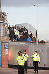 "Police officers standing on guard as Southampton fans make their way into the away end at Fratton Park stadium through a closed-off street before Portsmouth take on local rivals Southampton in a Championship fixture. Around 3000 away fans were taken directly to the game in a fleet of buses in a police operation known as the ""coach bubble"" to avoid the possibility of disorder between rival fans. The match ended in a one-all draw watched by a near capacity crowd of 19,879."