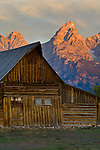 Sunrise light on the Grand teton mountain peak over old wooden barn, Mormon Row, Grand Teton National Park, Wyoming