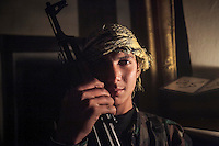 Said, a sixteen years old rebel fighter poses for photo as he holds his kalashnikov at Bustan Al-Qasr neighborhood, a frontline fierce punished by heavy artillery and one of the rebel's stronghold of Aleppo, Syria.