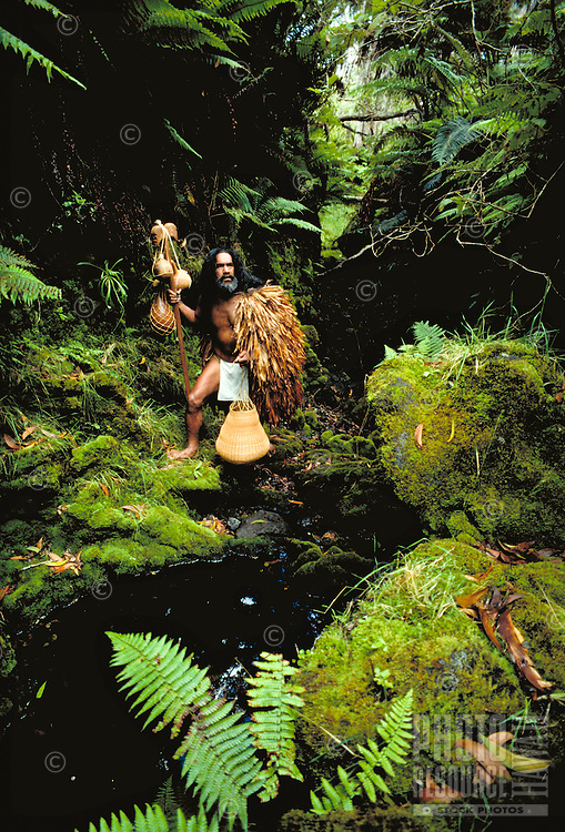 Hawaiian man in native rainforest in traditional cloak and water gourd