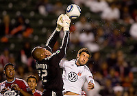 CD Chivas USA Zach Thornton leaps high over DC United forward Chris Pontius (of Servite high school & UCSB) for a save on his way to a clean sheet. CD Chivas USA beat DC United 1-0 at Home Depot Center stadium in Carson, California on Sunday August 29, 2010.
