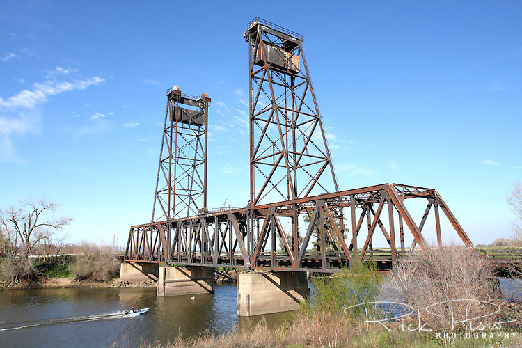 The original railroad bridge at Mossdale Crossing in California's Central Valley, completed in 1869, was the first bridge to cross the San Joaquin River and the last piece of the transcontinental railroad to be completed. Replaced in the early 1940's, trains still cross the bridge but it is unknown when the last time the vertical lift bridge was raised. Photographed 03/08