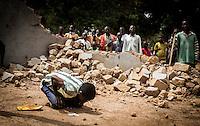 Ein christlicher Dorfbewohner aus dem Dorf Zere im Norden der Zentralafrikanischen Republik imitiert in der zerstörten Moschee des Ortes islamische Gebete. Im Hintergrund beobachten ihn andere Dorfbewohner. Aufnahmedattum 11.3.2014
