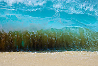 A large shorebreak wave sucks up the sand as it crashes onto Ke Iki beach, on the North Shore of Oahu.