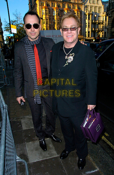 DAVID FURNISH & ELTON JOHN.The Old Vic Theatre Fundraiser VIP lunch, 50 St. James restaurant, London, UK..November 21st, 2006.full length sunglasses shades bags goody black couple blue suit black scardf striped stripes.CAP/CAN.©Can Nguyen/Capital Pictures