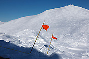 Appalachian Trail - Orange flagging marks tent lines on the summit of Mount Monroe during the winter months in the White Mountains, New Hampshire USA. Mount Washington is in the background.