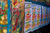 """Just-finished music party posters are seen drying on the scribbled wall in the sign painting workshop in Cartagena, Colombia, 14 April 2018. Hidden in the dark, narrow alleys of Bazurto market, a group of dozen young men gathered around José Corredor (""""Runner""""), the master painter, produce every day hundreds of hand-painted posters. Although the vast majority of the production is designed for a cheap visual promotion of popular Champeta music parties, held every weekend around the city, Runner and his apprentices also create other graphic design artworks, based on brush lettering technique. Using simple brushes and bright paints, the artisanal workshop keeps the traditional sign painting art alive."""