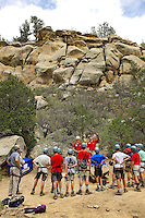 Photo story of Philmont Scout Ranch in Cimarron, New Mexico, taken during a Boy Scout Troop backpack trip in the summer of 2013. Photo is part of a comprehensive picture package which shows in-depth photography of a BSA Ventures crew on a trek.  In this photo BSA Venture Crew Scouts listen to climbing instructions before starting to climb onto the natural rock face at Dean Cow Camp, in the backcountry at Philmont Scout Ranch.   <br /> <br /> The  Photo by travel photograph: PatrickschneiderPhoto.com
