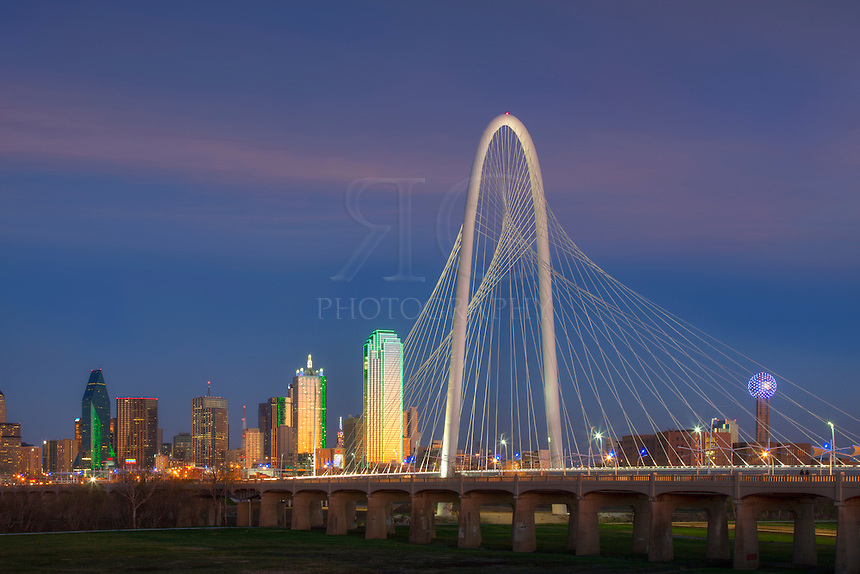 The Margaret Hunt Hill Bridge lights up at night with the skyline of Dallas, Texas, in the background. To the right is the iconic Reunion Tower. The tallest building in Dallas is the Bank of America Plaza at 921 feet.
