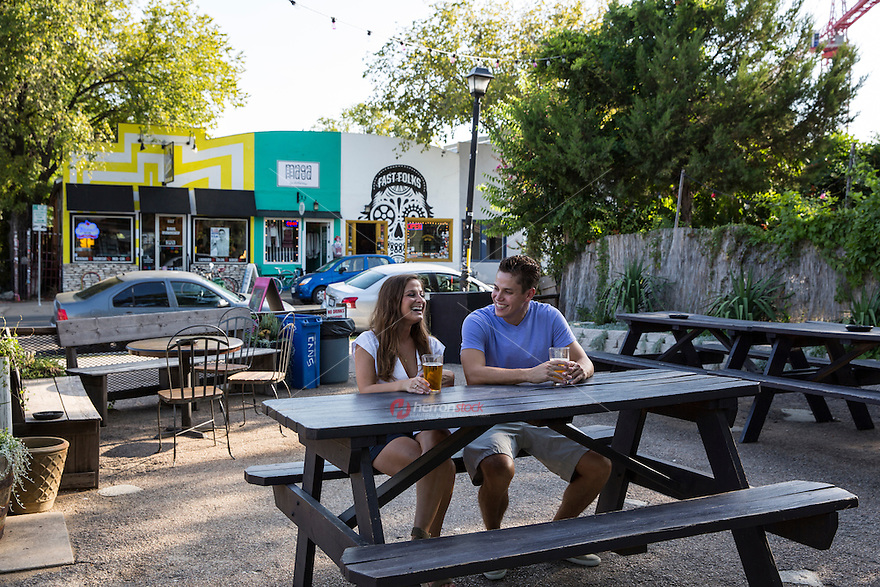 Young cheerful dating couple drinking beer at outdoor patio on East 6th Street in East Austin on a warm summer's day.