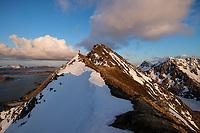 Hiker on narrow summit ridge of Slettind mountain peak, Flakstadøy, Lofoten Islands, Norway