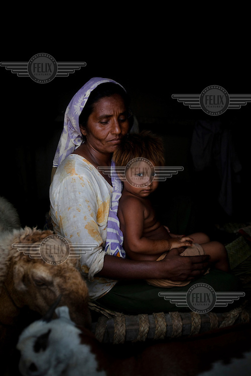 Cash grant recipient, Anwar Bibi, 40, sits in her hut with her child, Sassi, 3.