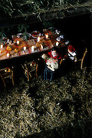 View looking down from the hayloft to a rustic candlelit table and a little girl with a lamb on her lap