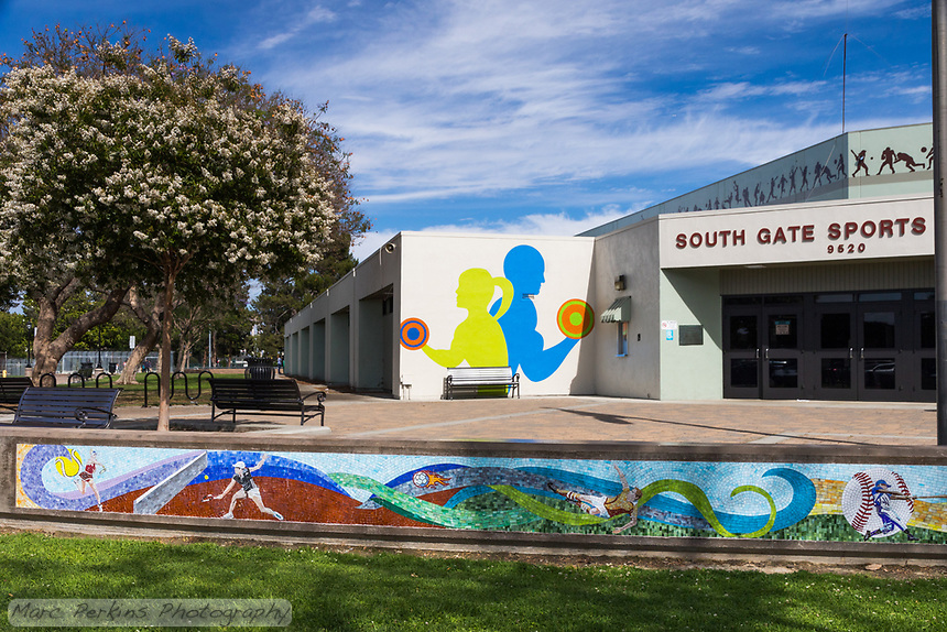 The South Gate Sports Center at South Gate Park, complete with sports mural, flowering trees, and painted monochromatic silhouettes of athletes.