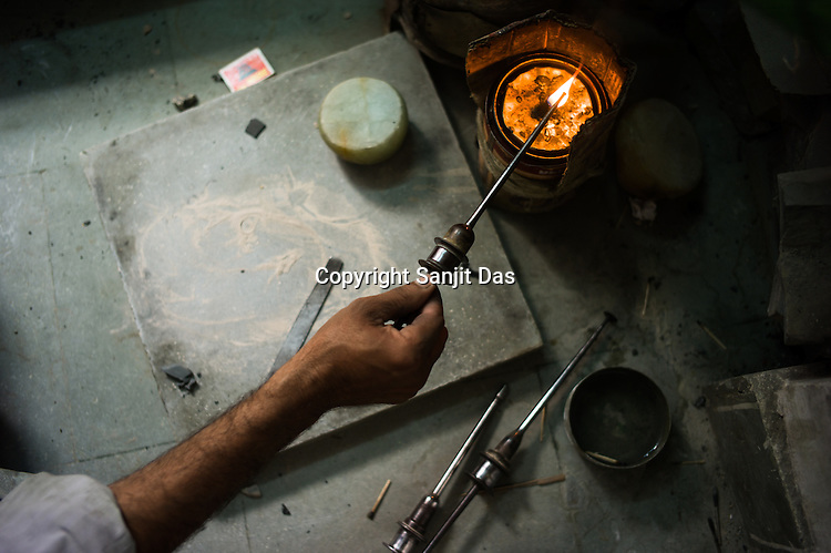 A worker is seen making instruments for polishing gem stones for fine jewelry at  a workshop in Sanganer in Jaipur, Rajasthan, India.  Photo: