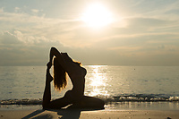 Silhouette of a girl in pigeon pose, practicing yoga on the beach, Thailand