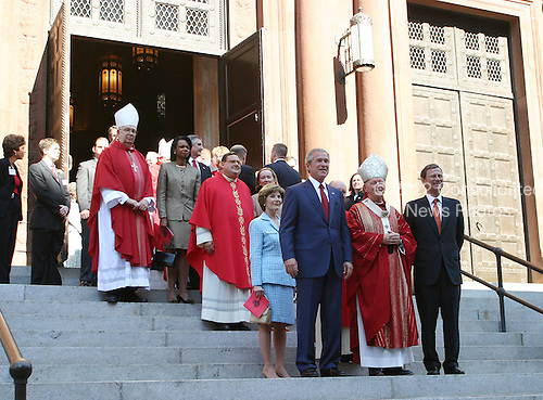 Washington, D.C. - October 2, 2005 - United States President George W. Bush attends 52nd Annual Red Mass at St. Matthews Cathedral.  Red Mass is a tradition that is held the Sunday prior to the Supreme Court's opening session.  The service gives special prayers for the court and the judges as they start hearing this session's cases.   This mass is special in that the new Chief Justice, John G. Roberts, Jr. was in attendance along with his wife Jane.  First lady Laura Bush was in attendance as well as United States Secretary of State Condoleezza Rice and White House Chief of Staff Andrew Card.  Cardinal Theodore McCarrick, Archbishop of Washington, presides over mass and then walked out of the church at the end of the ceremony and stood on the steps next to President Bush and Chief Justice John Roberts.  Left to right - front row: President Bush, Cardinal McCarrick, Chief Justice Roberts;  first lady Laura Bush is in the second row; Jane Roberts is in the third row behind Mrs. Bush; and Secretary Rice is in the fourth row..Credit: Gary Fabiano - Pool via CNP