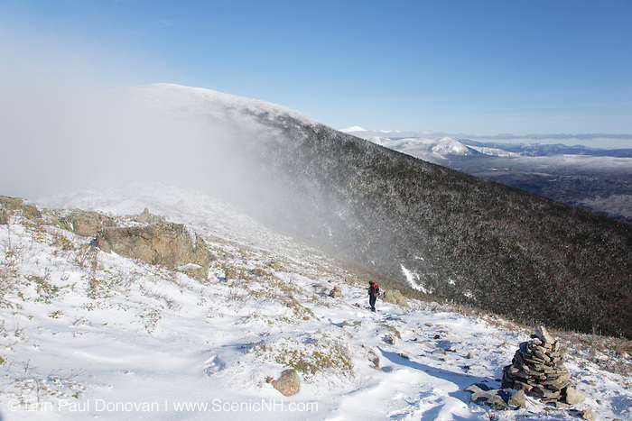A hiker on the summit of Bondcliff in the Pemigewasset Wilderness of the New Hampshire White Mountains during the winter months. Mount Bond is in the background
