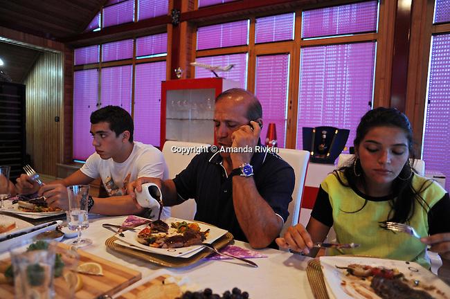 Ibrahim Ibrahimov (center) talks on his cell phone as he sits at the dinner table and eats steak with his son Huseyn Ibrahimov, 18, and daughter Ilkana Ibrahimova, 22, in his home between Sangachal and Sahil, Azerbaijan on August 16, 2012.