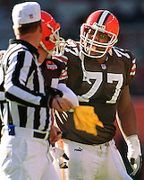 Cleveland Browns offensive tackle #77 Orlando Brown (right) with his right eye swollen shut, screams at referee Jeff Triplette who hit Brown with a thrown penalty flag.  Triplette had accidentally hit Brown in the eye with a penalty flag and Brown then confronted and attacked Triplette.